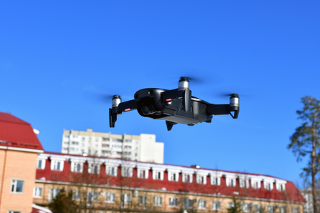 Black unmanned aerial vehicle with a camera against the blue sky.