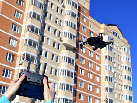 Quadrocopter flies in the sky and hands with a control panel.