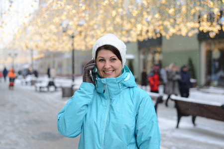 woman talking on phone on city street in winter