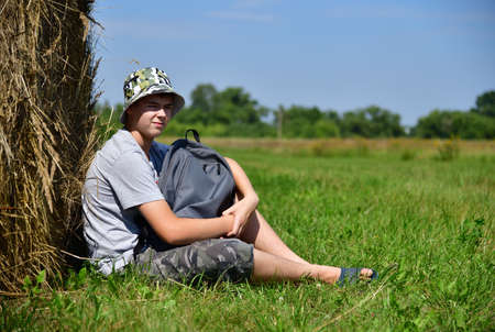 teenager with a backpack sitting next to a stack of straw