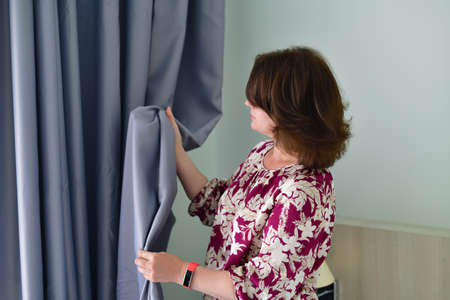 woman is standing next to a gray curtains