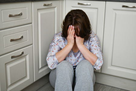 woman is sitting on the kitchen floor covering her face with her hands. Depression, grief or frustration