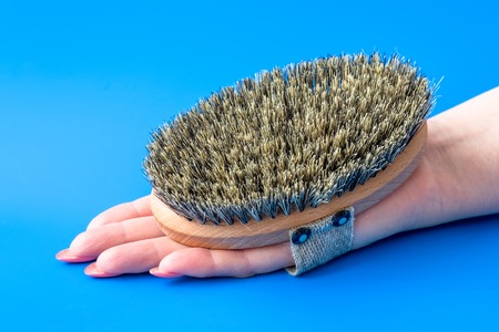 Brush with bristles made of horsehair on female hand 免版税图像 - 122431375