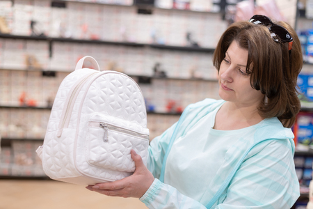 The Woman chooses bag backpack in the store