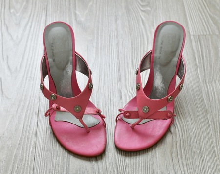Old pink heeled sandals stand on the floor