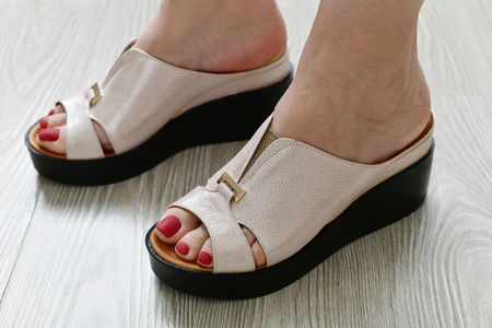 The Womens legs in summer white clogs