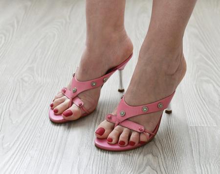 Damenbeine in sommerlichen rosa Sandaletten Standard-Bild