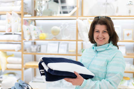woman chooses a towel in the store