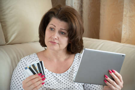 A woman is upset by online shopping with a bank card 写真素材