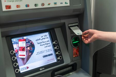 Abu Dhabi, UAE - March 29. 2019. A man's hand picks up a paper check from an ATM of Abu Dhabi Commercial Bank