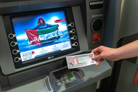 Abu Dhabi, UAE - March 29. 2019. 100 dirham in a hand against background ATM of Abu Dhabi Commercial Bank