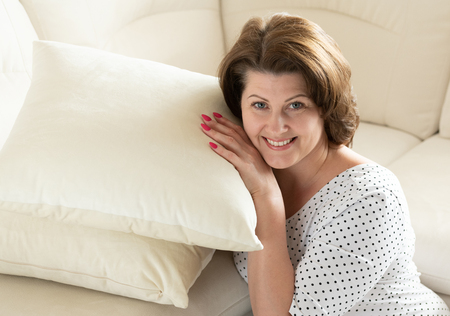 Smiling woman sitting with pillow by the sofa Banco de Imagens - 124981330