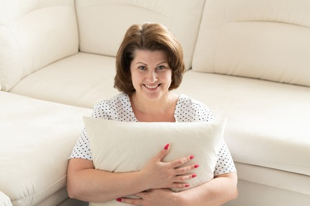 Smiling woman sitting with pillow by the sofa Banco de Imagens - 124980576