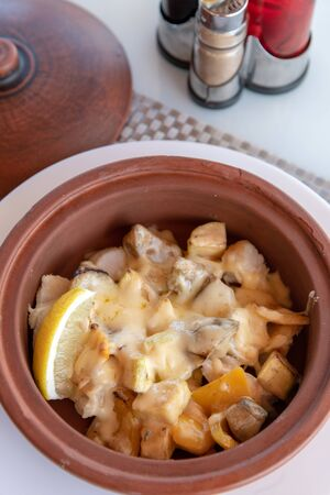 White fish baked with potatoes and a cheese Imagens