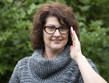 Portrait of curly woman in red glasses on nature