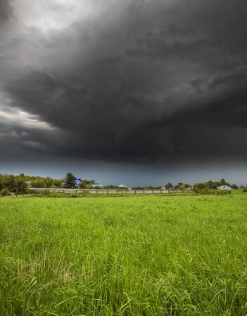 The Summer countryside landscape with a storm cloud Фото со стока