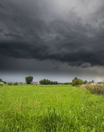 The Summer countryside landscape with a storm cloud Imagens