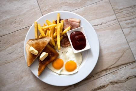 Fried eggs with toast and a french fries for breakfast