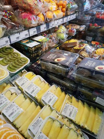 Moscow, Russia - Jan 27. 2020. Pineapples and other fruits in plastic containers at Perekrestok store