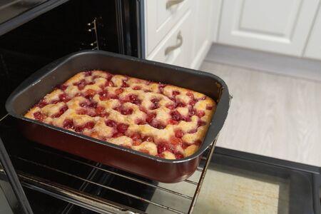 Baked cherry pie on baking sheet in the oven Stock fotó