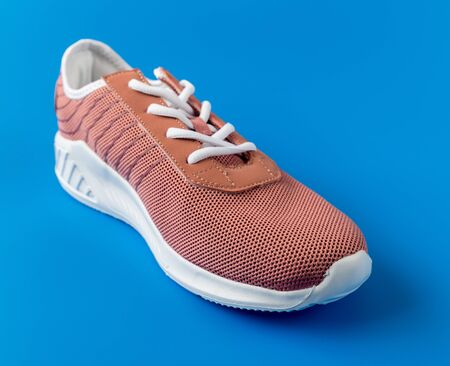 Brown textile sneakers on blue background.