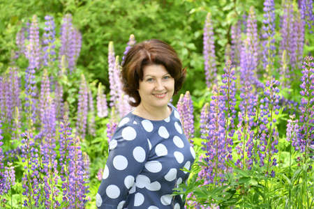 Woman in clearing among blooming lupins