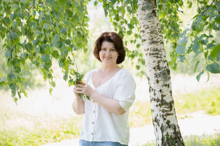 Russian woman with phone near the birch in the summer
