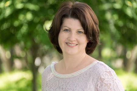 brunette woman near tree in summer park