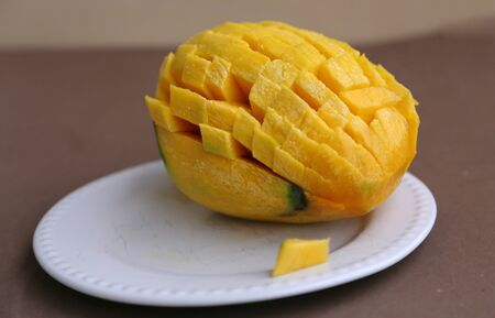 Large sugar tropical mango fruit with no skin ready to eat on white plate look side view Фото со стока