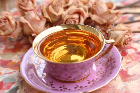 Pink cup with tea with golden bottom and little roses on pink background on Valentine's Day Banco de Imagens - 142115912