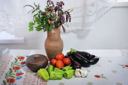 On the table lies a towel with poppies and cornflowers. There is an earthenware jug on the towel in which a bouquet of herbs and purple bisil, as well as green leaf sprigs celery. Near the jug is a clay pot with a lid. Nearby are vegetables: Bulgarian green peppers, eggplants, tomatoes and garlic. A white lace curtain is visible at the back.