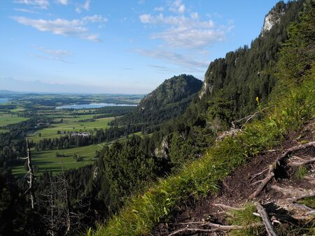 Panoramic photo of beautiful german land nature. Trees, lakes, meadows, fields from bird's-eye flight view. Scenic tourist route on the Alpine mountains. Mood of freedom, activity, journey, adventure.