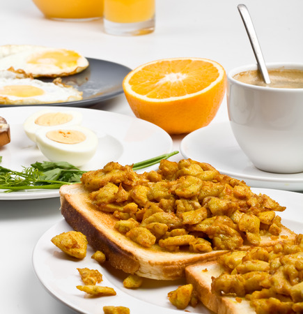 burnt toast: breakfast meal - scrambled eggs on toast, hard-boiled eggs, fried eggs, half of an orange and a cup of coffee