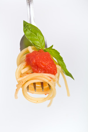 spaghetti with tomato sauce and green basil on a fork photo