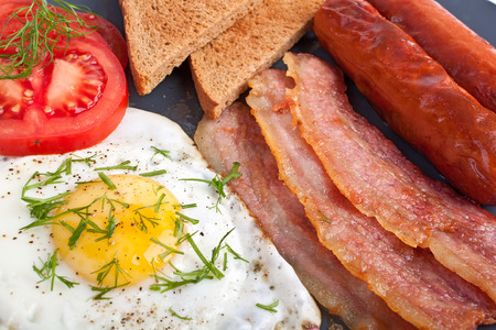 classic breakfast with fried egg, sausages, bacon and toast Stock Photo