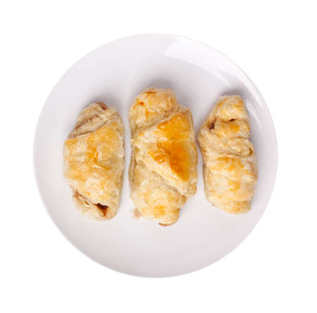 three sausage rolls on a white plate with more rolls at the background on dark plates photo
