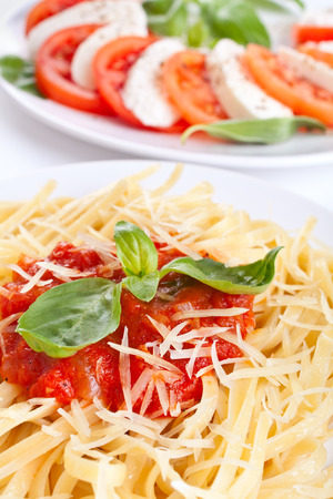 Linguine pasta with tomato sauce, cheese and basil and caprese salad in the back photo