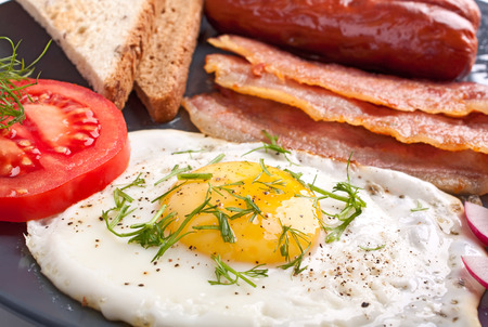 english breakfast: classic breakfast with fried egg, sausages, bacon and toast Stock Photo