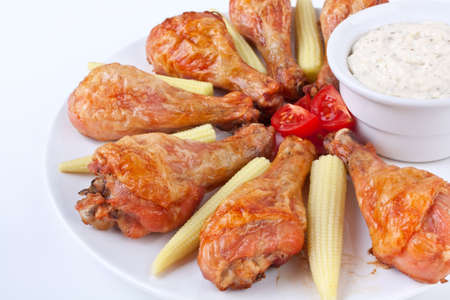 buffalo chicken legs served with cream sauce, cherry tomatoes and baby-corn photo