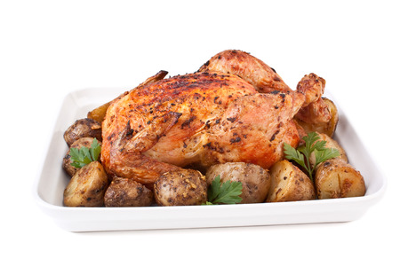 whole golden roasted chicken with roasted potatoes and parsley isolated photo