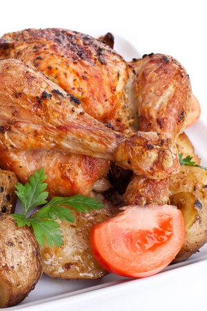 whole golden roasted chicken with roasted potatoes, fresh tomatoes and parsley photo