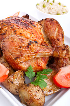 whole golden roasted chicken with roasted potatoes, fresh tomatoes and rice with peas photo