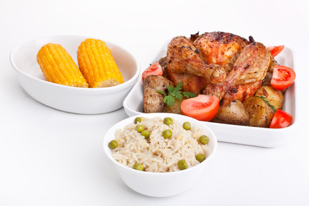 whole golden roasted chicken with roasted potatoes, fresh tomatoes, corn and rice with peas photo