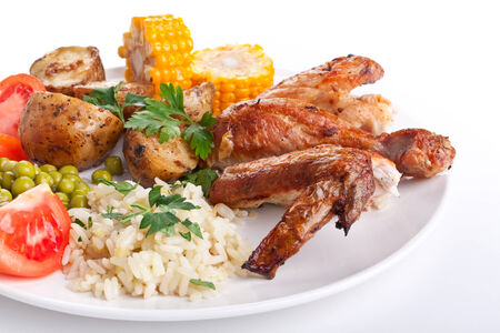 roasted chicken wings and legs with roasted potatoes, fresh tomatoes, corn and rice with peas photo