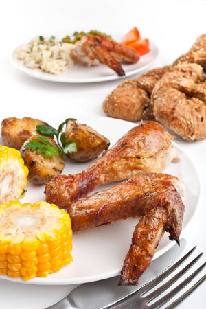 roasted chicken wings and legs with roasted potatoes, corn and bread photo