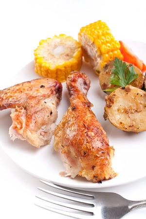 roasted chicken wings and legs with roasted potatoes and corn photo