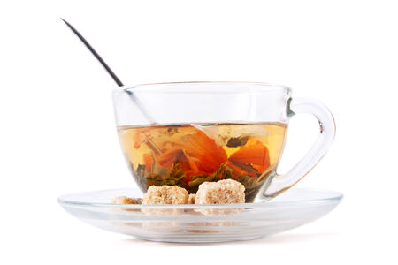 green tea with flowers in a glass cup with three brown sugar cubes photo
