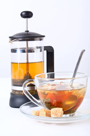 a cup of green tea with chrysanthemum and a french press photo