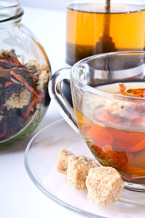 a cup of flower tea with chrysanthemum, dry tea in a jar and a french press photo