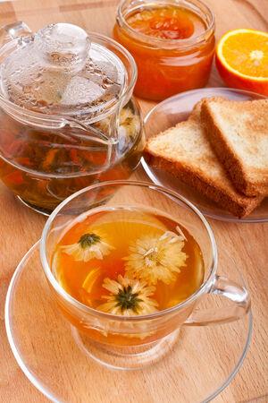 glass cup with chrysanthemum green tea, toasts, jam and tea-pot